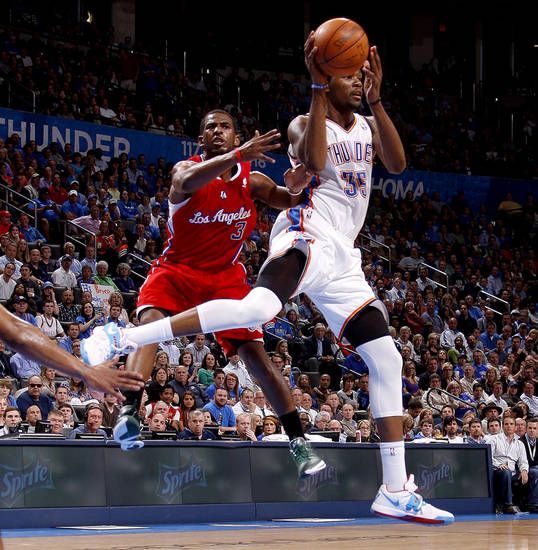Oklahoma City's Kevin Durant (35) passes the ball beside Los Angeles' Chris Paul (3) during the NBA basketball game between the Oklahoma City Thunder and the Los Angeles Clippers at Chesapeake Energy Arena in Oklahoma City, Wednesday, April 11, 2012. Photo by Bryan Terry, The Oklahoman