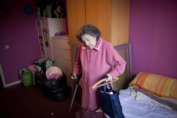 File - In this Nov. 18, 2011file photo, Azucena Paredes' grandmother Tomasa Morcillo, 87, picks up her personal belongings as she and her family are evicted from their home in Madrid. The Spanish government Thursday Nov. 15, 2012 passed a decree curbing evictions of lower income homeowners unable to pay their mortgage, a bid to ease a trend that has seen hundreds of thousands of people lose their homes because of the brutal economic crisis. The urgent measure stops evictions for two years of people whose unemployed benefits have expired or who have incomes of less than �1,200 ($1,527) a month after tax and whose mortgage represents at least 50 percent total household income. Public attention on the issue intensified greatly in recent weeks after two homeowners facing eviction committed suicide. Spaniards are also angry because while people lose their homes, the government is negotiation billion-dollar bailouts for the same banks who are repossessing the houses. Over the past four years, social groups have begun organizing street protests to try to avoid prevent court officials and police carrying out eviction orders. (AP Photo/Arturo Rodriguez, File)