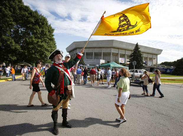 William Temple, of Brunswick, Georgia, waves a flag outside Hilton Coliseum before the Iowa Republican Party's Straw Poll, Saturday, Aug. 13, 2011, in Ames, Iowa. (AP Photo/Charlie Neibergall)