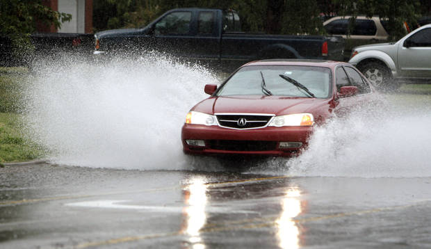 A car plows through flash flood waters along Britton Road in Oklahoma City, OK, Saturday, August 18, 2012,  By Paul Hellstern, The Oklahoman