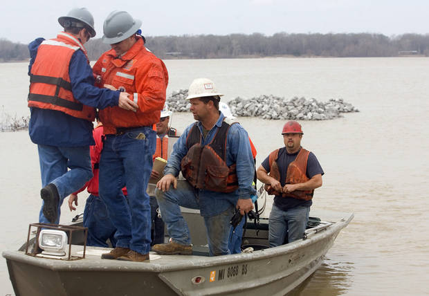 Shannon Warnock, far right, a salvage hand with Big River Ship Builders &amp; Salvage, secures his flotation device after loading a boat with MDEQ employees at Le Tourneau Landing to work on the damaged barge stalled on the west bank of the Mississippi River,  Monday, Jan. 28, 2013 near Vicksburg, Miss.   A barge carrying thousands of gallons of oil struck a railroad bridge and began leaking before dawn Sunday. The accident forced the closure of a 16-mile stretch of the lower Mississippi, a major inland corridor for vessels carrying oil, fuel, grain and other goods. (AP Photo/The Vicksburg Evening Post, Melanie Thortis )  MANDATORY CREDIT