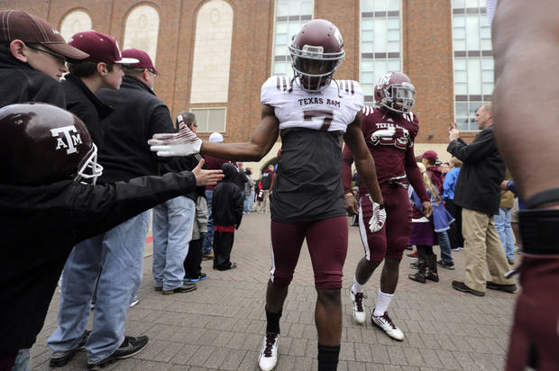 Fans greet Texas A&M defensive back Tramain Jacobs (7) as he walks to practice with teammates for the Cotton Bowl NCAA college football game, Sunday, Dec. 30, 2012, in Dallas. Texas A&M is scheduled to play Oklahoma on Jan. 4, 2013. (AP Photo/LM Otero) ORG XMIT: TXMO121