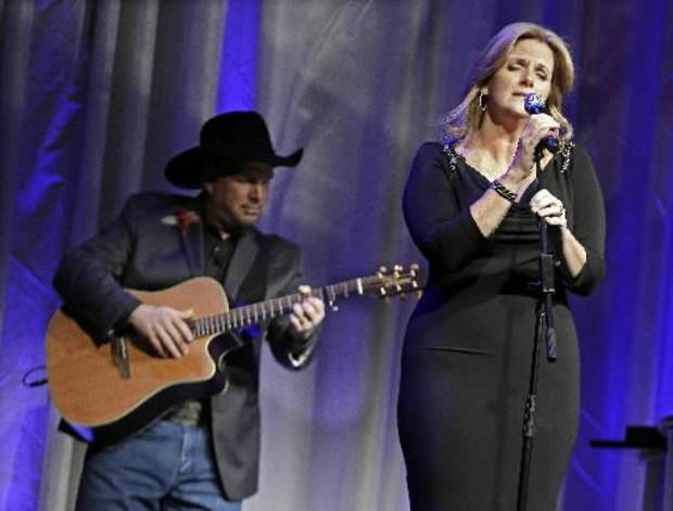 "Trisha Yearwood is accompanied by her husband, Garth Brooks, as she sings ""Wind Beneath My Wings,"" a song written by Larry Henley, as Henley is inducted into the Nashville Songwriters Hall of Fame on Sunday, Oct. 7, 2012, in Nashville, Tenn. (AP photos)"