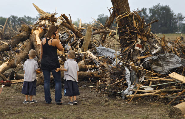 Kirby Easter and her sons Josh and Jacob try to find anything salvageable in the debris left behind after the home of Tom Chronister was destroyed north of El Reno, Tuesday, May 24, 2011. Photo by Chris Landsberger, The Oklahoman ORG XMIT: KOD