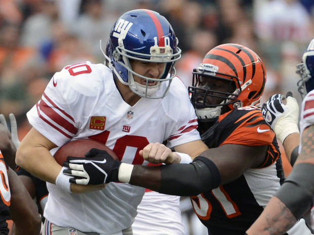 New York Giants quarterback Eli Manning (10) is sacked by Cincinnati Bengals defensive end Robert Geathers (91) in the first half of an NFL football game on Sunday, Nov. 11, 2012, in Cincinnati. (AP Photo/Michael Keating)