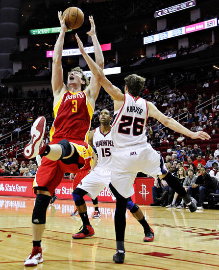 Houston Rockets center Omer Asik (3) and Atlanta Hawks guard Kyle Korver (26) battle for a rebound during the first half of an NBA basketball game, Monday, Dec. 31, 2012, in Houston. (AP Photo/Bob Levey)