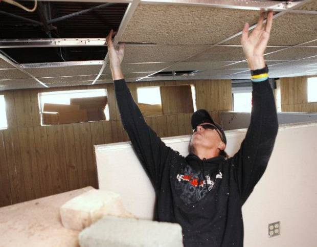 Randy Swanson installs ceiling tiles Saturday as members of Southern Nazarene University's class of 1980 work to help Love Link Ministries Inc. prepare to move into a new building in downtown Oklahoma City. PHOTO BY PAUL HELLSTERN, THE OKLAHOMAN <strong>PAUL HELLSTERN</strong>