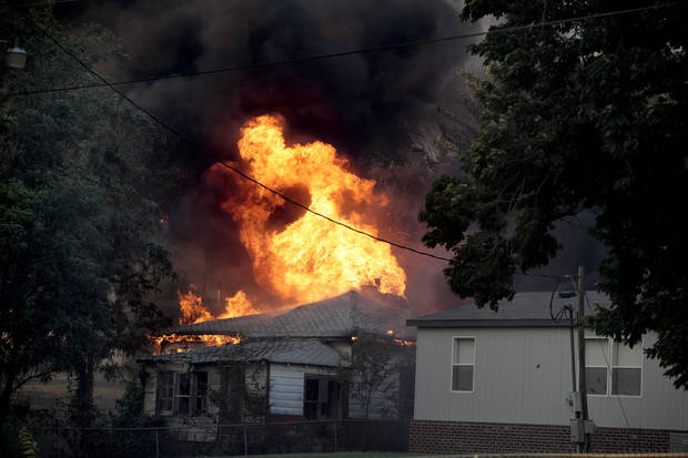 A home burns in Luther, Okla.,  during a large wildfire Friday, Aug. 3, 2012. <strong>SARAH PHIPPS - THE OKLAHOMAN</strong>