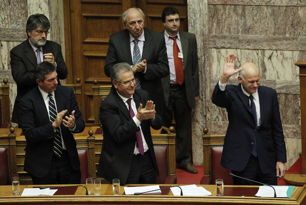 Lawmakers applaud Greek Prime Minister George Papandreou, right, as he waves after his speech during a parliament session in Athens, Thursday, Nov. 3, 2011. Papandreou abandoned his explosive plan to put a European rescue deal to popular vote Thursday, keeping his government alive _ but passionate squabbling in Athens left the country's solvency in doubt and the eurozone in turmoil. Greek Prime Minister reversed course after a rebellion within his own Socialist party over the referendum, but ignored repeated calls to resign and call elections. (AP Photo/Petros Giannakouris) ORG XMIT: XPG117