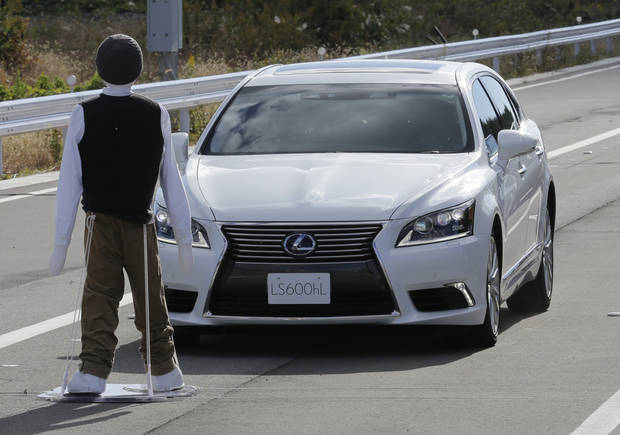 Toyota's Lexus LS stops automatically in front of a dummy during a Toyota Motor Corp. demonstration of the pre-collision system (PCS) at its Higashi-Fuji Technical Center in Susono, southwest of Tokyo, Monday, Nov. 12, 2012. The PCS, one of the automaker's pedestrian accident countermeasures, watches out for pedestrians to avoid collisions with them. (AP Photo/Koji Sasahara)