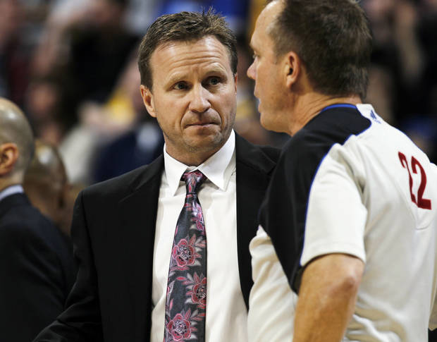 Oklahoma City Thunder head coach Scott Brooks, left, confers with referee Bill Spooner on a call in the first quarter of an NBA basketball game against the Denver Nuggets in Denver, Sunday, Jan. 20, 2013. (AP Photo/David Zalubowski)
