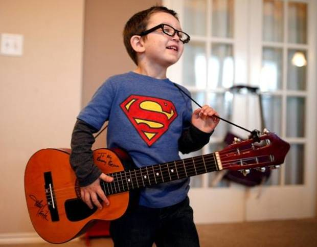 Brock Hart, 5, a former cancer patient, plays guitar at his Edmond home. Oklahoma country music superstar gave the boy the guitar and autographed it. Photo by Sarah Phipps