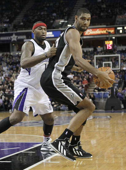 San Antonio Spurs forward Tim Duncan, right, goes to the basket against Sacramento Kings center DeMarcus Cousins during the first quarter of an NBA basketball game in Sacramento, Calif., Friday, Nov. 9, 2012. (AP Photo/Rich Pedroncelli)