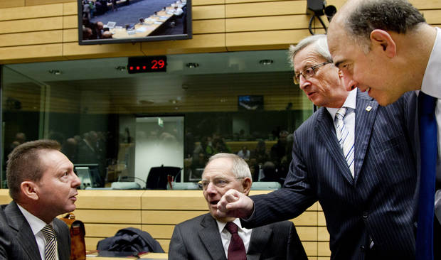 Luxembourg&#039;s Prime Minister Jean-Claude Juncker, second right, playfully gestures toward Greek Finance Minister Yannis Stournaras, left, during a meeting of eurogroup finance ministers in Brussels on Thursday, Dec. 13, 2012. The European Union on Thursday took a major step towards one of the most important transfers of financial authority away from national capitals when its member states agreed to create a single supervisor for their banks. At center is German Finance Minister Wolfgang Schaeuble, and at right is French Finance Minister Pierre Moscovici. (AP Photo/Virginia Mayo)