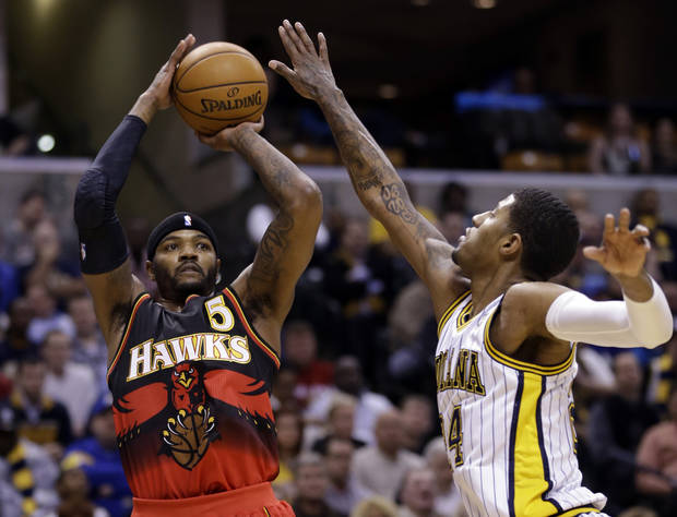 Atlanta Hawks forward Josh Smith, left, shoots over Indiana Pacers forward Paul George during the first half of an NBA basketball game in Indianapolis, Tuesday, Feb. 5, 2013. (AP Photo/Michael Conroy)