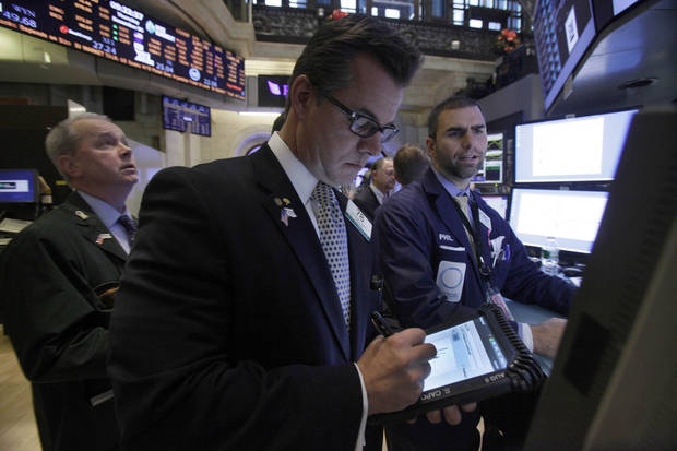 Trader Steven Capo, center, works on the floor of the New York Stock Exchange Thursday, Dec. 6, 2012.  Stocks are opening mixed on Wall Street following news that Europe will hold off on new economic stimulus measures. (AP Photo/Richard Drew)