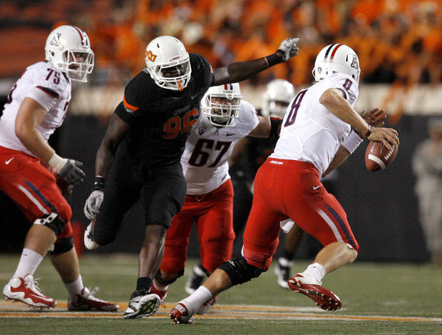 Oklahoma State's Ryan Robinson (96) pressures Arizona's Nick Foles (8) during a college football game between the Oklahoma State University Cowboys (OSU) and the University of Arizona Wildcats at Boone Pickens Stadium in Stillwater, Okla., Thursday, Sept. 8, 2011. Photo by Sarah Phipps, The Oklahoman  ORG XMIT: KOD