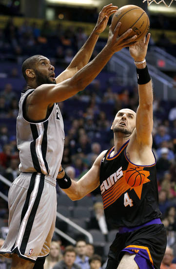San Antonio Spurs' Tim Duncan has his shot blocked by Phoenix Suns' Marcin Gortat, of Poland, during the first half of an NBA basketball game, Sunday, Feb. 24, 2013, in Phoenix. (AP Photo/Matt York)
