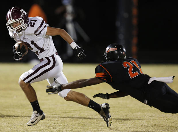 Ada's Chase Lott (21) runs past Douglass's Barry Knight (21) during a high school football game between Douglass and Ada at Moses F. Miller Stadium in Oklahoma City, Friday, Nov. 2, 2012.  Photo by Garett Fisbeck, The Oklahoman
