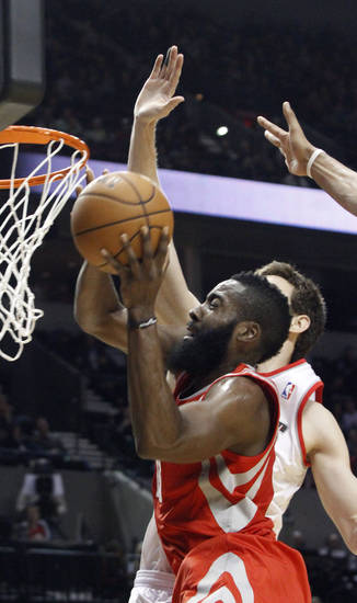 Houston Rockets guard James Harden, left, goes to the hoop against Portland Trail Blazers forward Victor Claver, from Spain, during the first half of their NBA basketball game in Portland, Ore., Friday, Nov. 16, 2012.(AP Photo/Don Ryan)