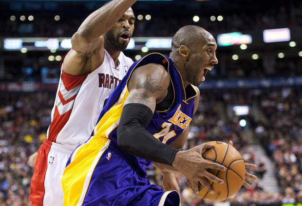 Los Angeles Lakers guard Kobe Bryant, right, drives the net past Toronto Raptors Alan Anderson, left, during first half NBA basketball action in Toronto on Sunday Jan. 20, 2013. (AP Photo/THE CANADIAN PRESS,Nathan Denette)