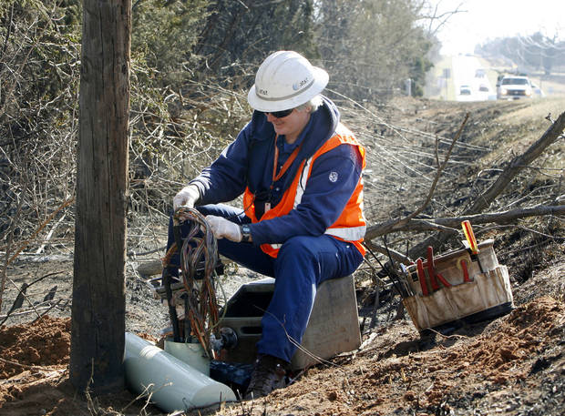 AT&T cable repairman Steve West works to restore service, Saturday, April 11, 2009, at a cable box which melted near the intersection of Reno and Hiwasee Roads in Choctaw, OK, during Thursday evening's wildfires. Photo by Paul Hellstern, The Oklahoman