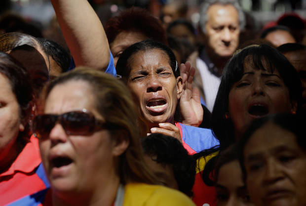 "Women react as they gather at Simon Bolivar square in support of Venezuela's President Hugo Chavez in Caracas, Venezuela, Sunday Dec.  9, 2012.  Chavez is to return to Cuba Sunday for another surgery in his battle against cancer, which has led him to speak publicly of a successor for the first time.  Chavez said Saturday that if there are ""circumstances that prevent me from exercising the presidency further""  Vice-President Nicolas Maduro should replace him for the remainder of his term.(AP Photo/Fernando Llano)"