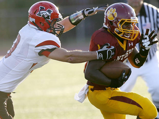 Putnam City North's Dre Holman tries to get away from Mustang's Steven Fruit during their high school football game at Putnam City Stadium in Oklahoma City on Thursday, September 8, 2011. Photo by John Clanton, The Oklahoman