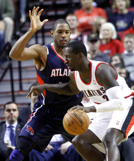 Portland Trail Blazers center J.J. Hickson, right, works the ball against Atlanta Hawks forward Al Horford during the first half of their NBA basketball game in Portland, Ore., Monday, Nov. 12, 2012. (AP Photo/Don Ryan)