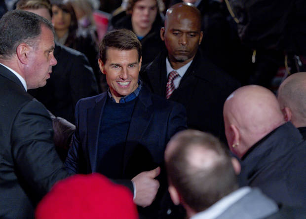 U.S actor Tom Cruise greets fans as he arrives on the red carpet for the UK Premiere of Mission: Impossible Ghost Protocol, at a central London cinema, Tuesday, Dec. 13, 2011. (AP Photo/Joel Ryan) ORG XMIT: LENT114