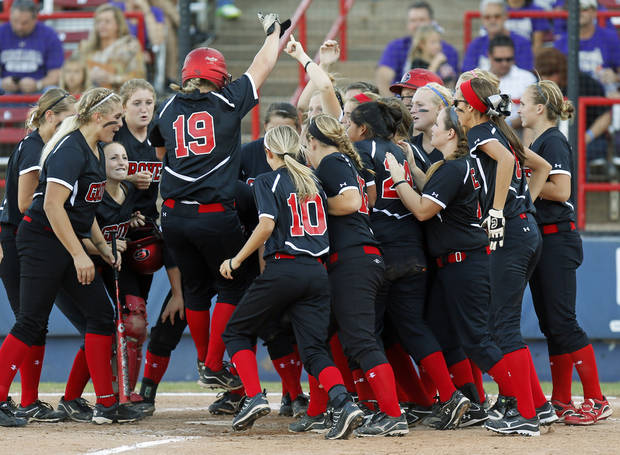 Grove's Jessica Walker (19) jumps on home plate while surrounded by her teammates after hitting a home run in the 4th inning during the 5A state championship fast-pitch softball game between Grove and Chickasha at ASA Hall of Fame Stadium in Oklahoma City, Monday, Oct. 15, 2012. Grove won, 3-2. Photo by Nate Billings, The Oklahoman