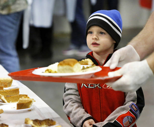 Dayton Cieszynski, 6, watches as a volunteer moves a tray carrying Dayton's food as the two go through the serving line. Dayton attended the event with his sister and a great aunt. Hundreds were served a traditional Christmas meal at the annual Red Andrews Dinner inside the Cox Convention Center on Christmas Day, Dec. 25, 2012. An army of  volunteers showed up despite  snow and ice and hazardous driving conditions. They accompanied each guest through the serving line and carried their trays and seated them at their tables. Other volunteers distributed a small mountain of toys and stuffed animals that were donated for the event.   Photo by Jim Beckel, The Oklahoman <strong>Jim Beckel - THE OKLAHOMAN</strong>