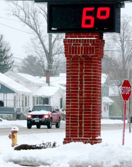 The thermometer on the Andover Bank in Austinburg Township in Ohio shows a temperature of 6 degrees Tuesday afternoon Jan. 22, 2013.  Waves of frigid Arctic air began sweeping south from Canada on Saturday night, locking the Midwest in a deep freeze that has left a section of the country well-acquainted with winter's pains reeling.   (AP Photo/The Star-Beacon, Warren Dillaway)
