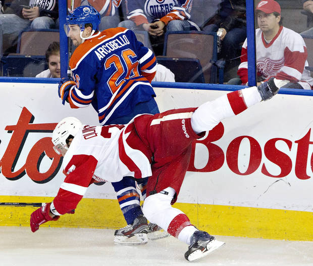 Detroit Red Wings' Kyle Quincey (27) is checked by Edmonton Oilers' Mark Arcobello (26) during the second period of an NHL hockey game in Edmonton, Alberta, on Saturday, Nov. 2, 2013. (AP Photo/The Canadian Press, Jason Franson)