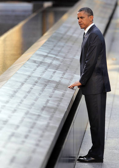 President Barack Obama touches the names etched into the memorial wall during his visit to the North Memorial Pond at the National Sept. 11th Memorial Sunday, Sept., 11, 2011 in New York. (AP Photo/Pablo Martinez Monsivais)