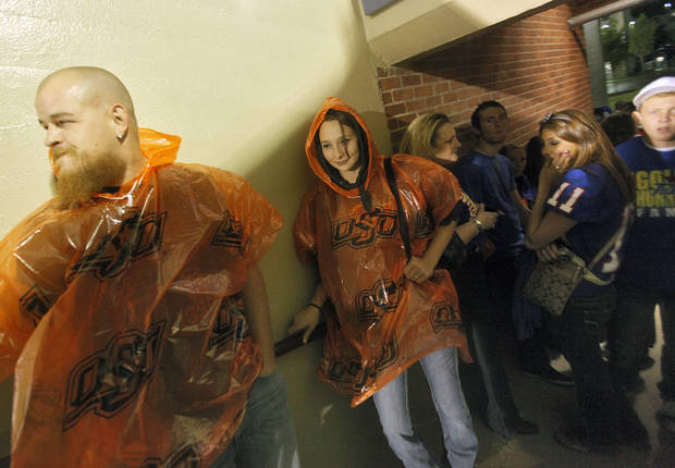 Tim Tandy and Brooke Umholt take cover in the concourse of the stadium as a storm delays the start of the college football game between Tulsa and Oklahoma State Photo by Chris Landsberger, The Oklahoman