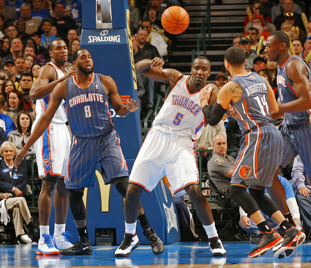 Charlotte Bobcats' D.J. White (8) watches as Oklahoma City Thunder's Kendrick Perkins (5) interrupts a pass from Charlotte Bobcats' D.J. Augustin (14) during the NBA basketball game between the Oklahoma City Thunder and the Charlotte Bobcats at Chesapeake Energy Arena in Oklahoma City, Saturday, March 10, 2012. Photo by Steve Sisney, The Oklahoman