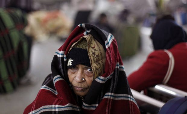 An elderly woman sits wrapped in a shawl as she waits for the arrival of a train at a railway station in Allahabad, India, Saturday, Dec. 29, 2012. North India continues to face extreme weather conditions with dense fog affecting flights and trains, according to local reports. (AP Photo/Rajesh Kumar Singh)