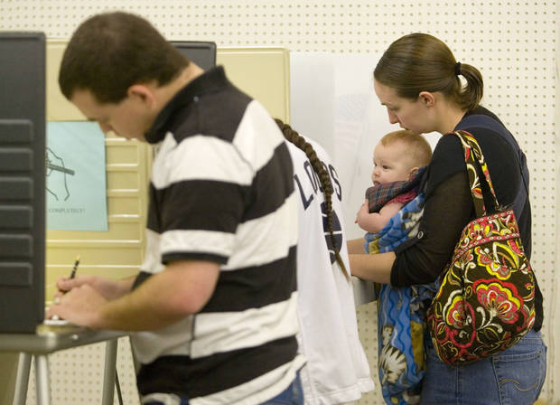 Cassandra Bradford, right, holds her three-month-old daughter, Camilla Bradford, while voting at the Latah County Fairgrounds in Moscow, Idaho, on Tuesday, Nov. 6, 2012. (AP Photo/Moscow-Pullman Daily News, Geoff Crimmins)