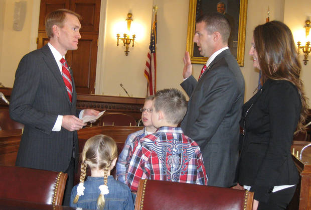 Rep. James Lankford, left, delivers a ceremonial oath of office on Capitol Hill on Thursday to new Rep. Markwayne Mullin, who was accompanied by his family. <strong>Chris Casteel - The Oklahoman</strong>