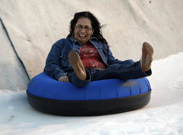 Mary Jane Flores rides down a snow slope at Chickasaw Bricktown Ballpark in Oklahoma City, Saturday, Nov. 24, 2012.  Photo by Garett Fisbeck, The Oklahoman