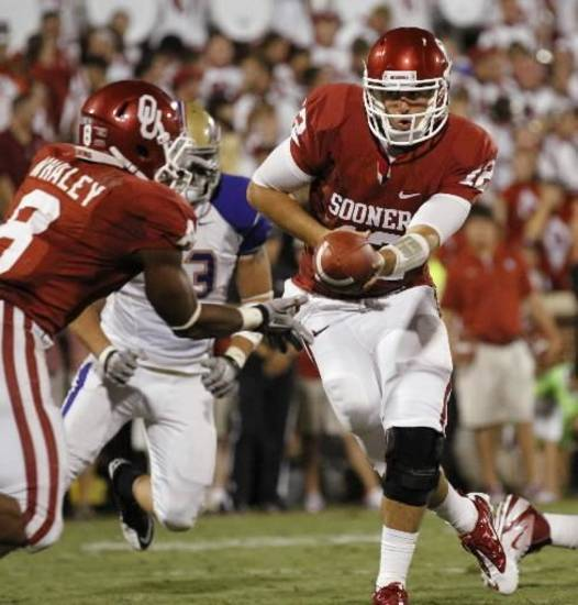 Oklahoma's Landry Jones (12) hands off to Dominique Whaley (8) during the second half of the college football game between the University of Oklahoma Sooners ( OU) and the Tulsa University Hurricanes (TU) at the Gaylord Family-Memorial Stadium on Saturday, Sept. 3, 2011, in Norman, Okla. Photo by Steve Sisney, The Oklahoman ORG XMIT: KOD