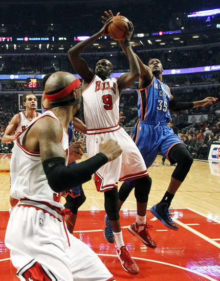 Chicago Bulls forward Luol Deng (9) shoots under pressure from Oklahoma City Thunder forward Kevin Durant (35) as Bulls' Richard Hamilton, foreground, watches during the first half of an NBA basketball game, Thursday, Nov. 8, 2012, in Chicago. (AP Photo/Charlie Arbogast) ORG XMIT: CXA104