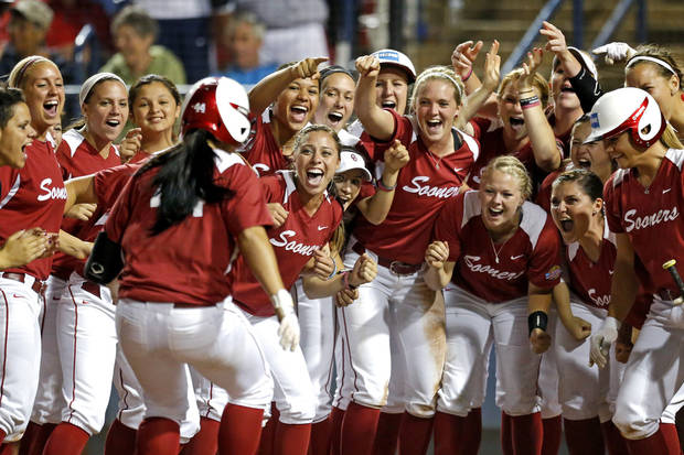 Oklahoma's Lauren Chamberlain is greeted at home after hitting a home run in the third inning against Washington during Women's College World Series softball game at ASA Hall of Fame Stadium in Oklahoma City, Sunday, June, 2, 2013. Photo by Sarah Phipps, The Oklahoman Download
