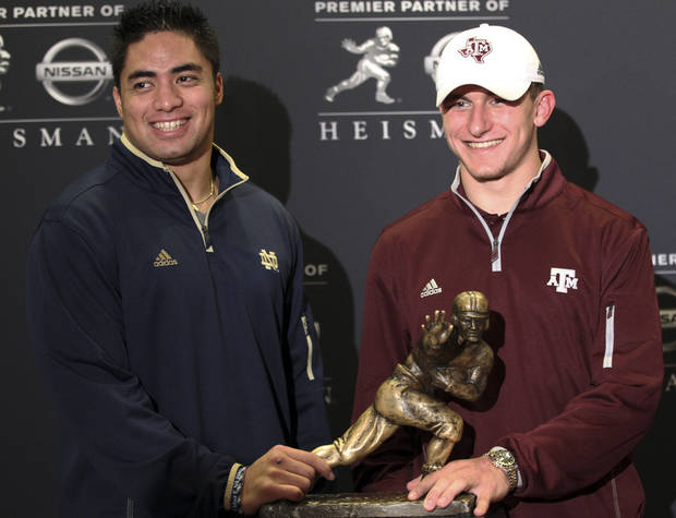 Notre Dame linebacker Manti Te'o, left, and Texas A&M quarterback Johnny Manziel, two of the three Heisman Trophy finalists, pose with the Heisman Trophy during a media availability, Friday, Dec. 7, 2012 in New York.  (AP Photo/Mary Altaffer)