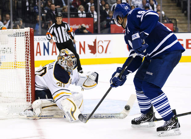 Toronto Maple Leafs forward Joffrey Lupul, right, gets spoke checked by Buffalo Sabres goalie Ryan Miller, left, during the second period of their NHL hockey game, Monday, Jan. 21, 2013, in Toronto. (AP Photo/The Canadian Press, Nathan Denette)