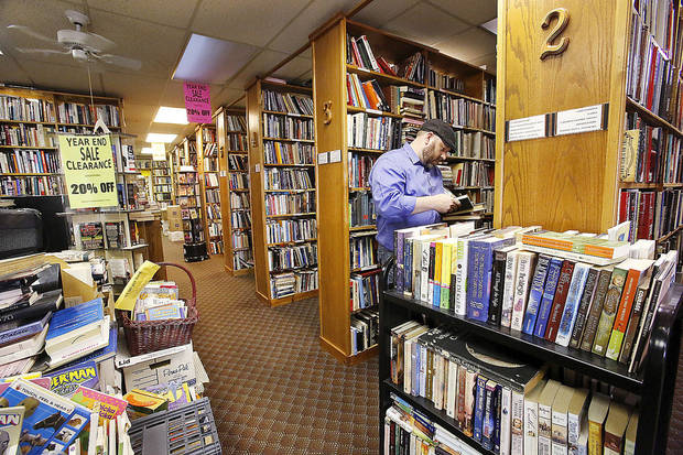 Clay Olson, of Oklahoma City, shops at the Aladdin Book Shoppe. The store remains open for customers after a Dec. 15 fire.