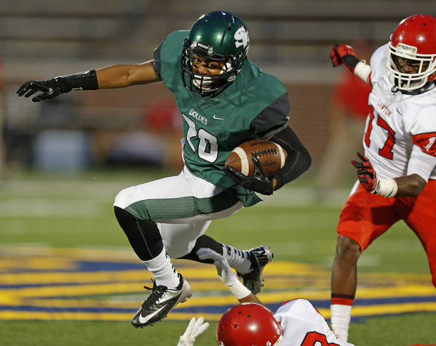 Edmond Santa Fe's Cameron Westbrook  leaps over Lawton's Kevin Bell as Kalin Sadler chases during their high school football game at Wantland Stadium in Edmond, Okla., Thursday, October 11, 2012. Photo by Bryan Terry, The Oklahoman