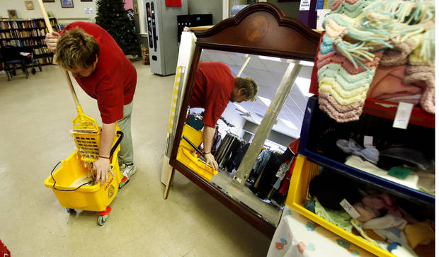 Employee Nathan Putnam mops the floor at ReRun Junction, a Norman thrift store run by disabled adults. PHOTO BY STEVE SISNEY, THE OKLAHOMAN <strong>STEVE SISNEY</strong>