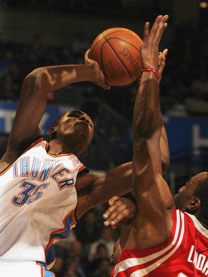 Kevin Durant shoots under the basket guarded  by Carl landry in the first half as the Oklahoma City Thunder plays the Houston Rockets at the Ford Center in Oklahoma City, Okla. on Friday, January 9, 2009. 